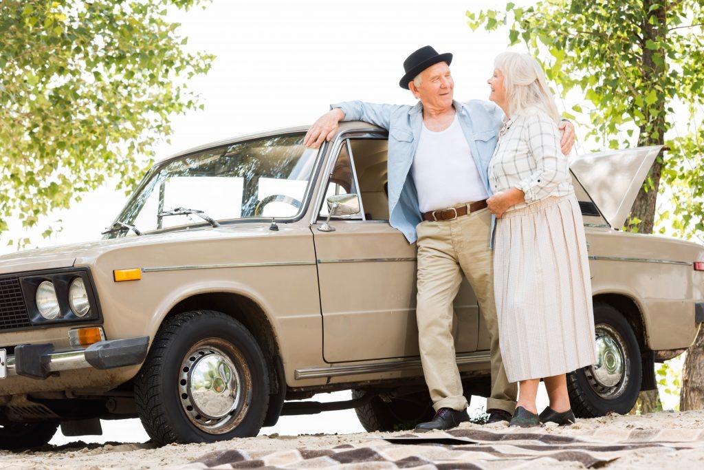 Eldre par står ved siden av veteranbil