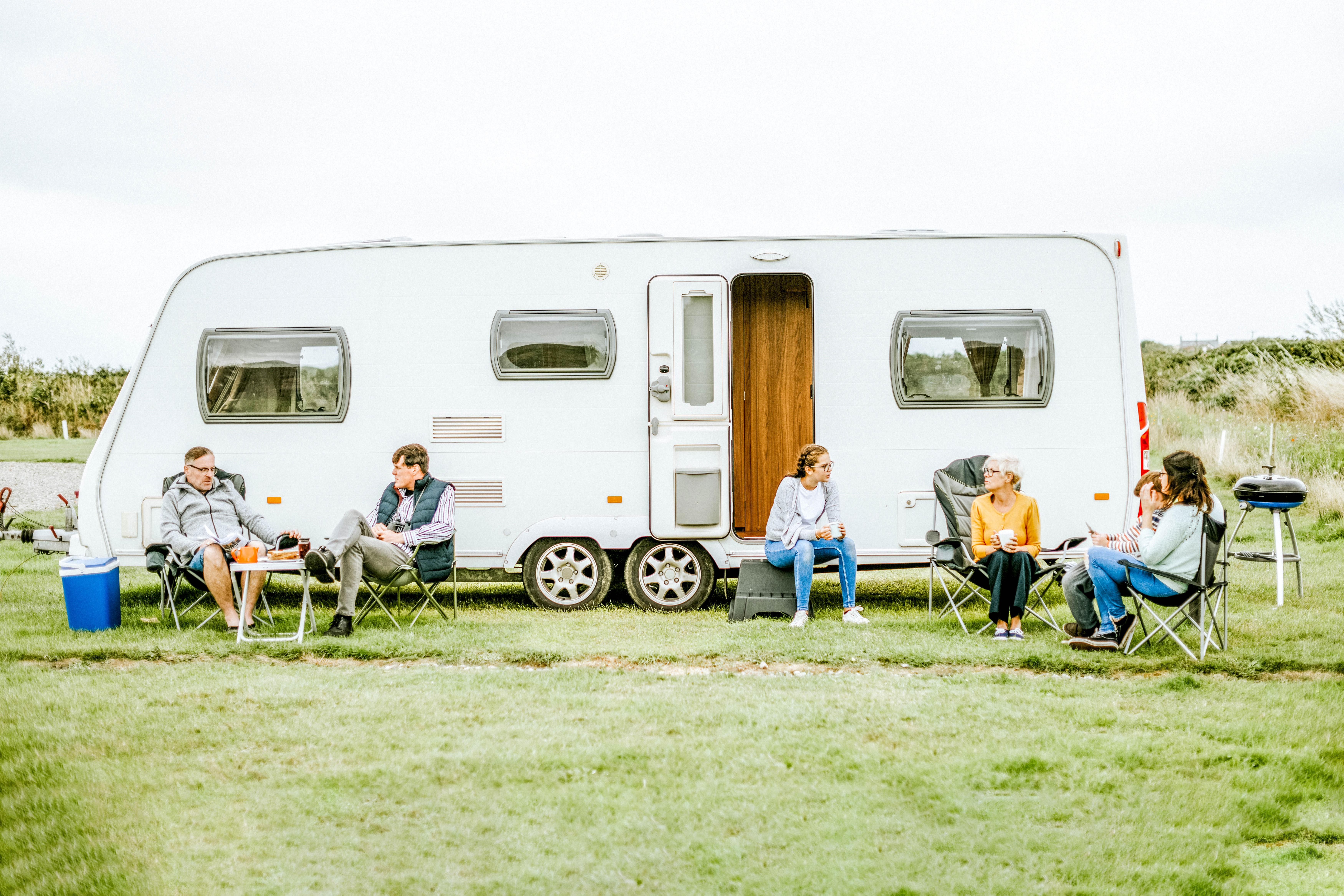 Mennesker sitter utenfor campingvogn